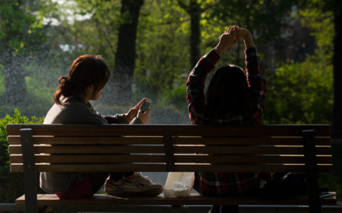people sitting on bench, one is using a smartphone