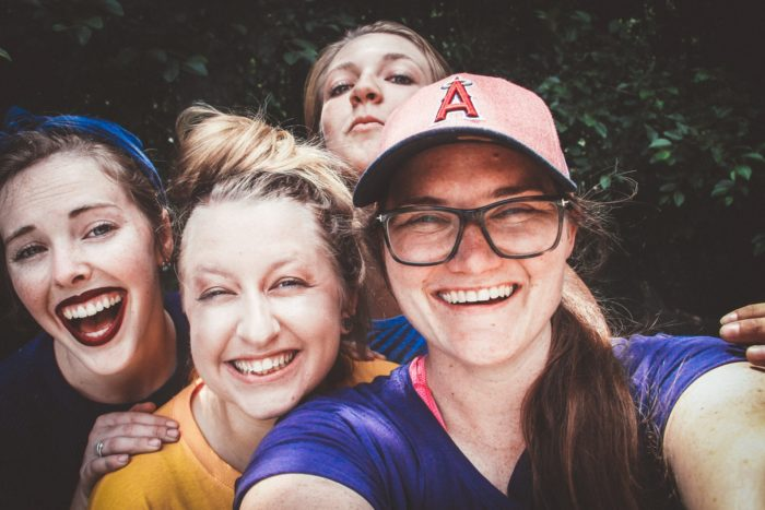 Smiling young woman taking selfie of herself and three friends
